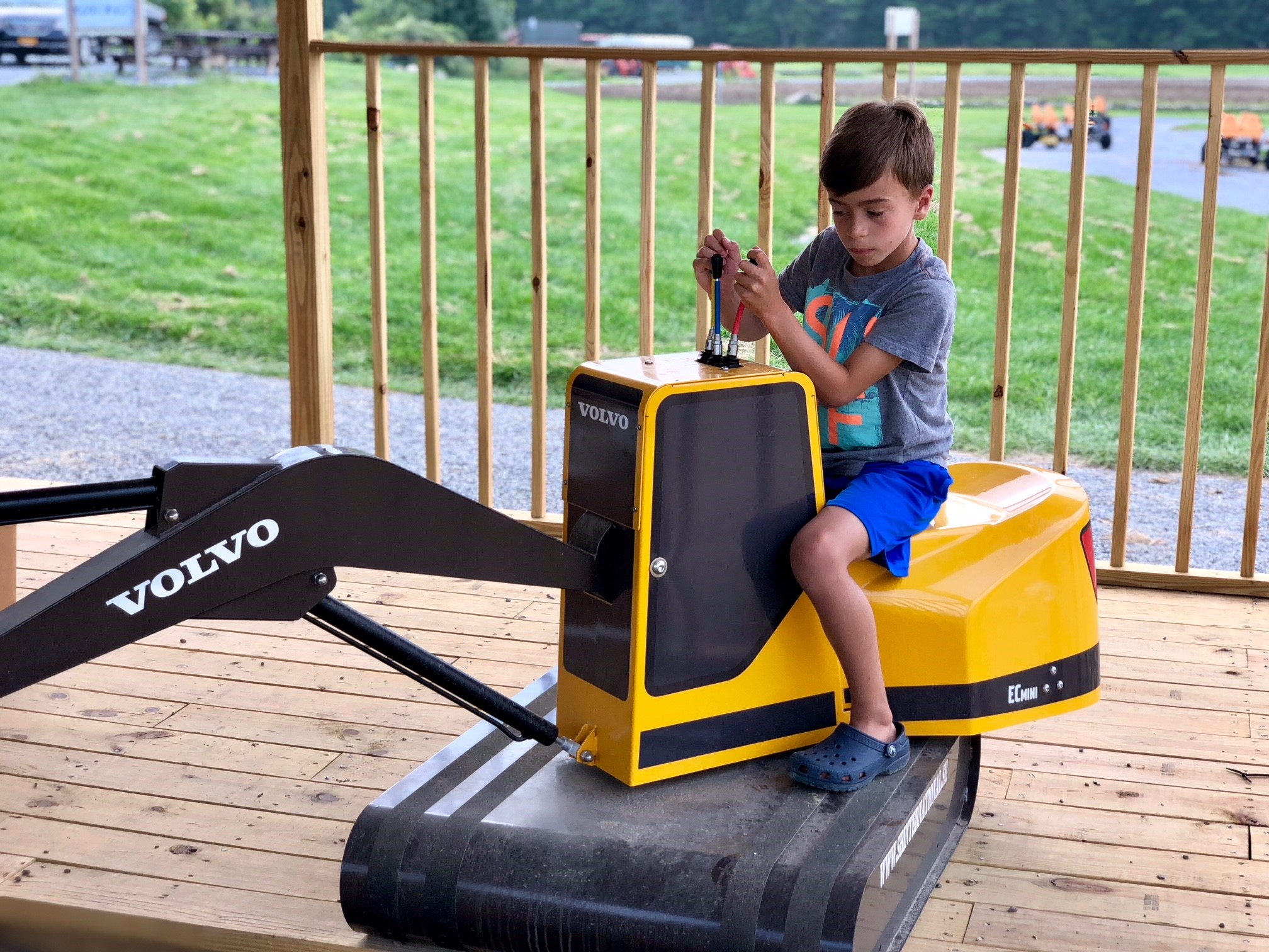 Boy using the controls of a mini excavator