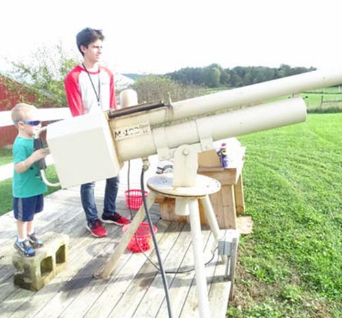 Adult supervises as small boy fired the Apple Canon at Ellms Farm