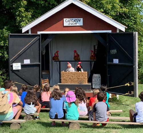 Families watching robotic chicken show at Ellms Farm in Saratoga