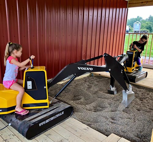 Two young girls using toy backhoes at Ellms Farm