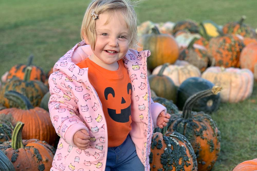 toddler in pink coat among pumpkins
