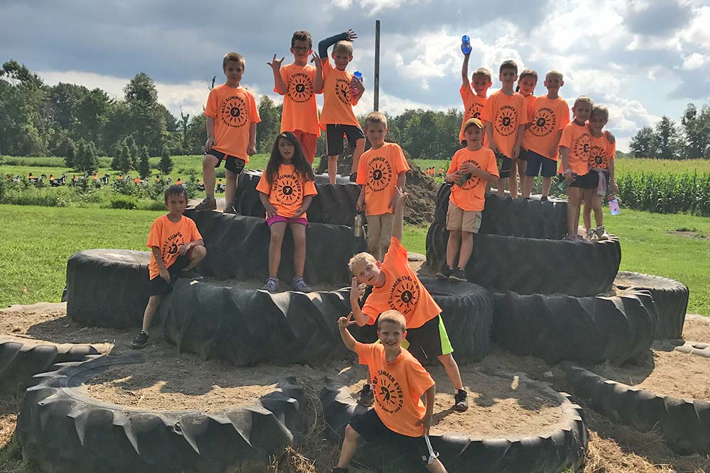 Group of kids climbing tower of tires