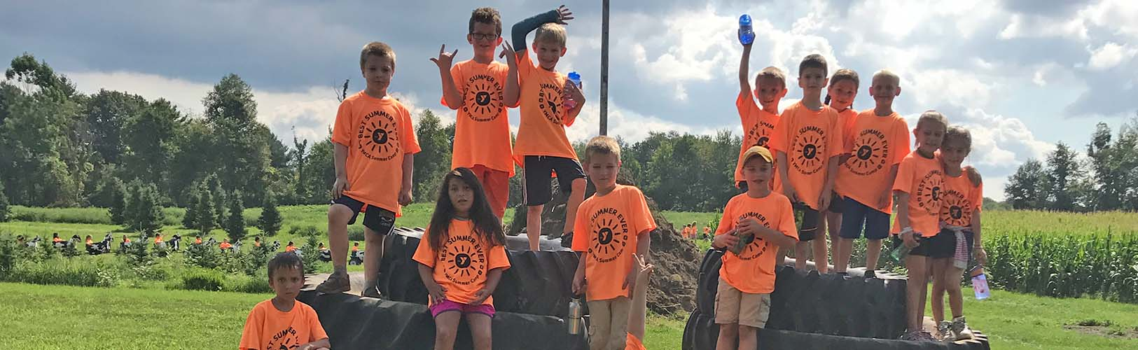 Kids in orange shirts on tire mountain
