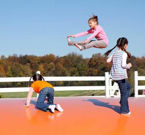 Children playing on a large jumping pillow