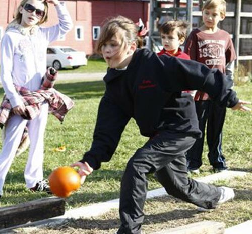 Young girl punpkin bowling at Ellms Family Farm in Saratoga County