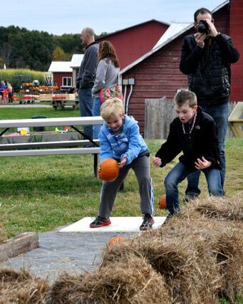 Young boys punpkin bowling at Ellms Farm in Ballston Spa while Dad snaps a photo