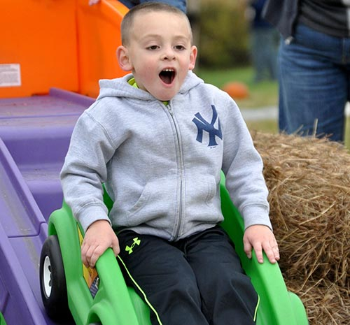 Boy in sweatshirt rides a rollercoaster at Ellms Farm