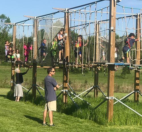 Parents watch children on the ropes challenge course