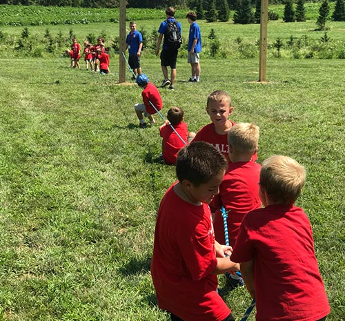 Kids in red shirts playing tug-of-war at Ellms Family Farm in Saratoga