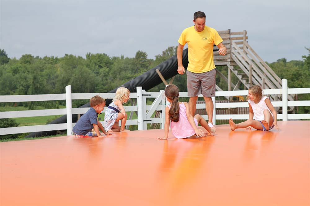 adult and kids on jumping pillow