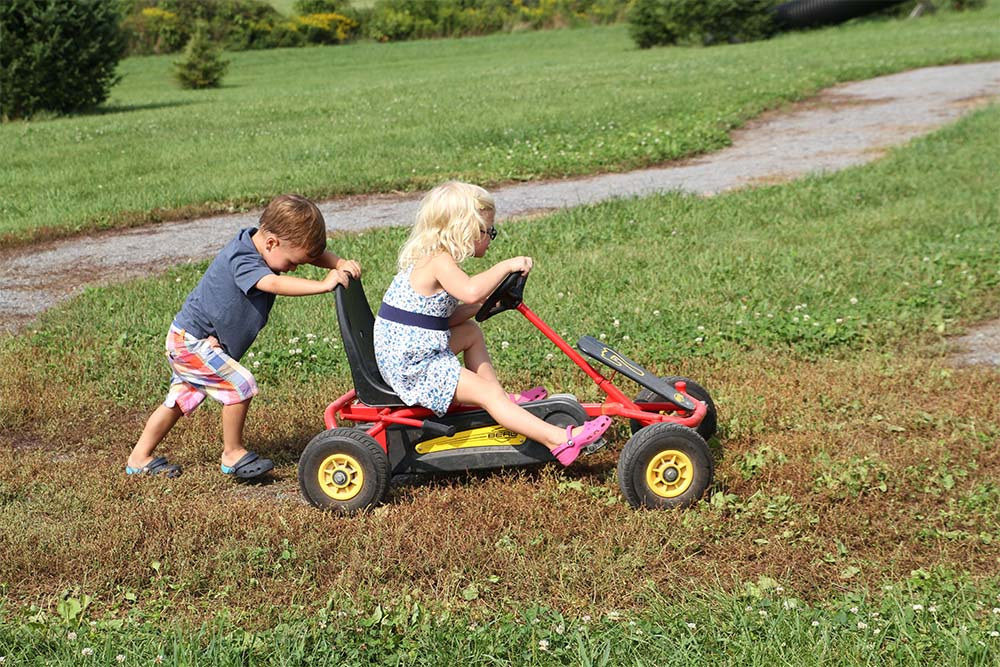 young boy pushing a girl on a pedal cart