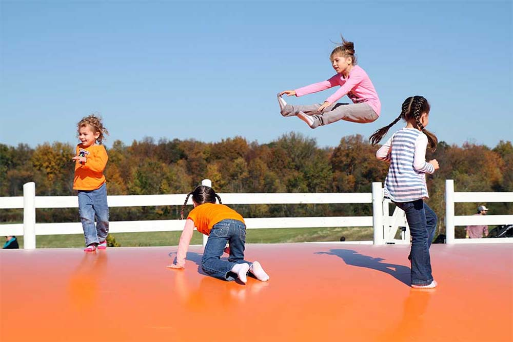 kids bouncing and jumping on jumping pillow