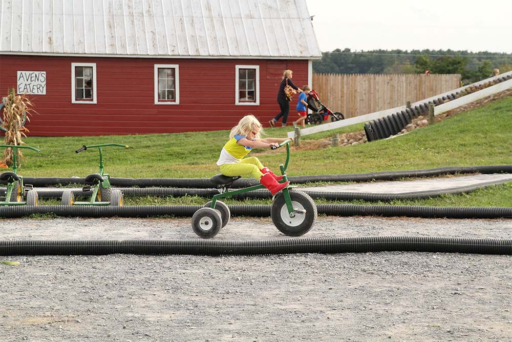 girl riding green tricycle on track