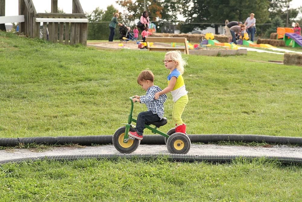 girl and boy riding tricycle