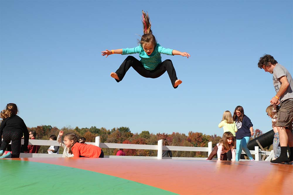 girl jumping high on jumping pillow