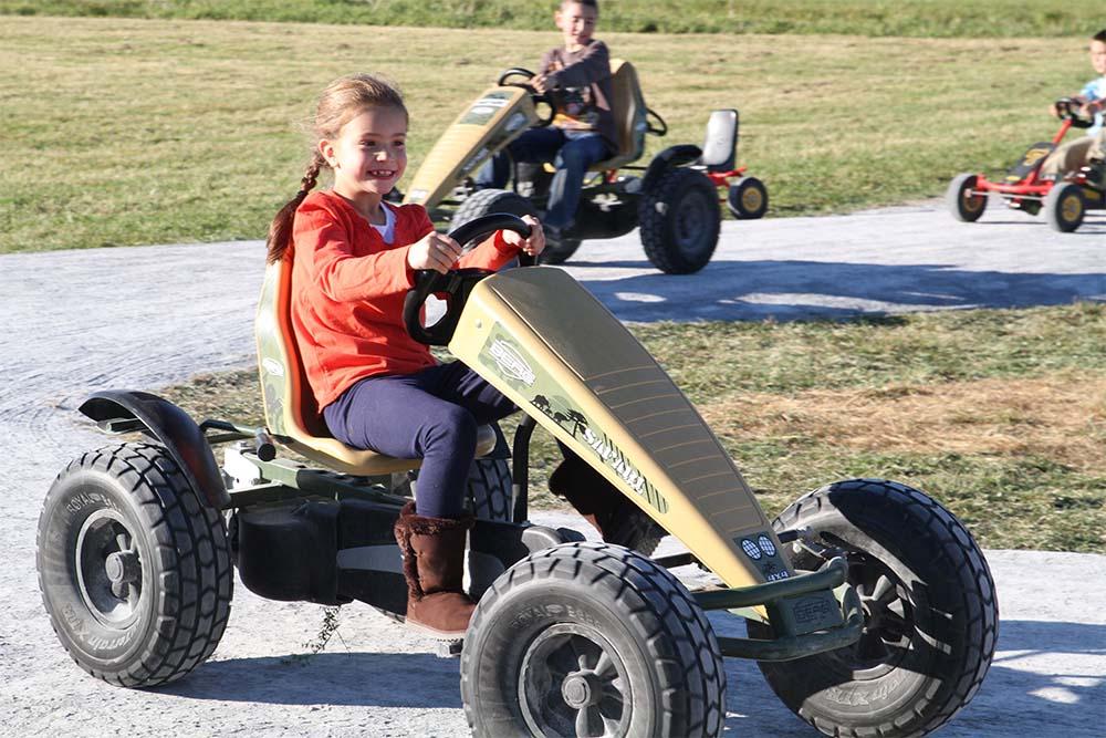 girl driving a pedal cart
