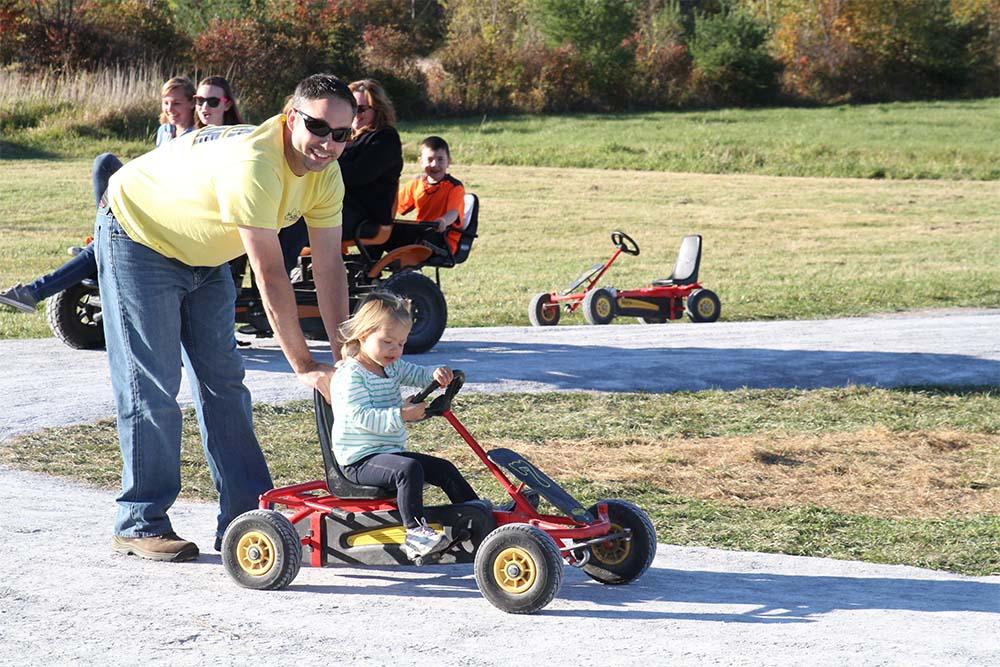dad pushing girl in pedal cart