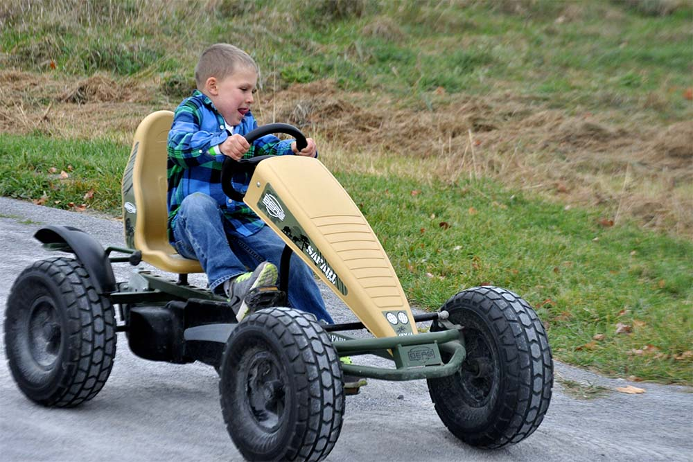 kid driving a pedal cart