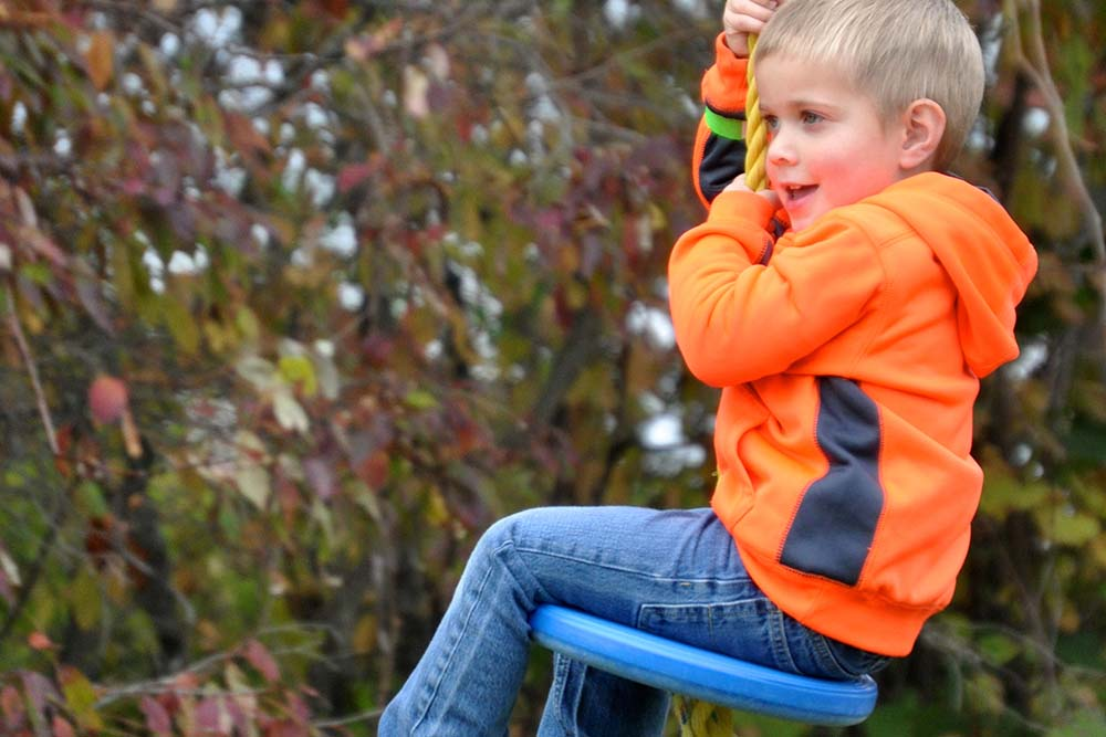boy in orange sweatshirt riding zipline