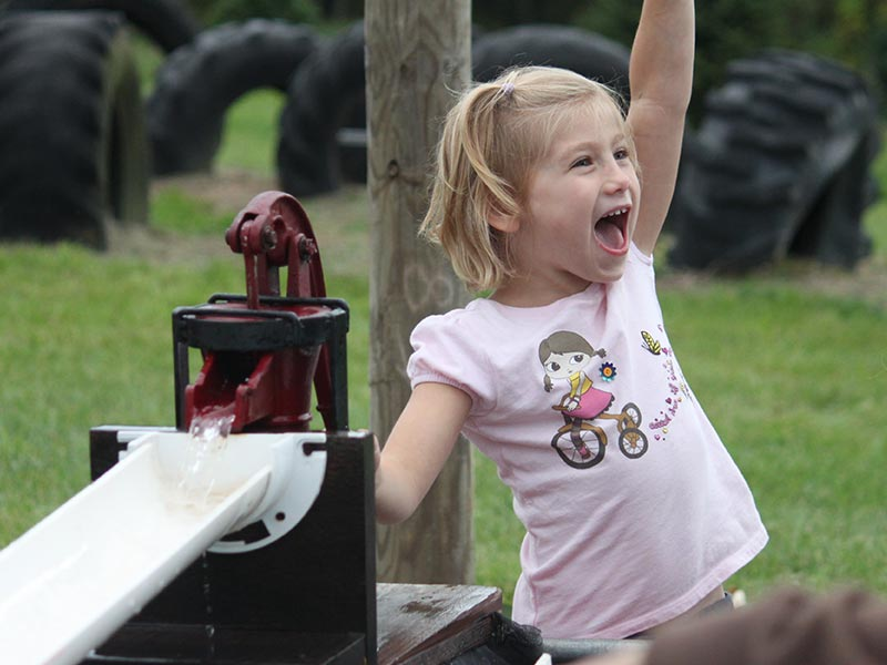 Little girl fist pumps her victory in the duck race