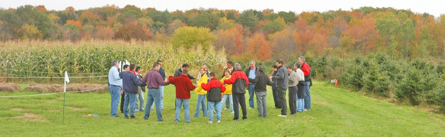 Company employees join hands in a circle outside the corn maze