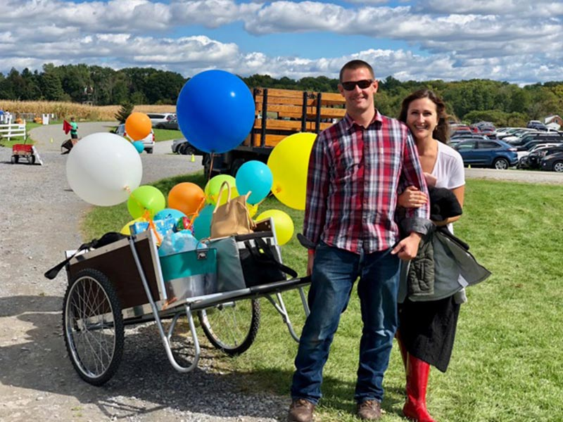 Man and woman pulling wheel barrow with presents and balloons
