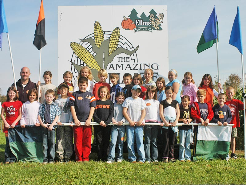Group of kids standing in front of The Amazing Maize sign at Ellms Farm in Saratoga