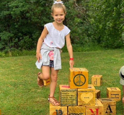 Young girl standing on letter blocks at Ellms Family Farm in Saratoga NY