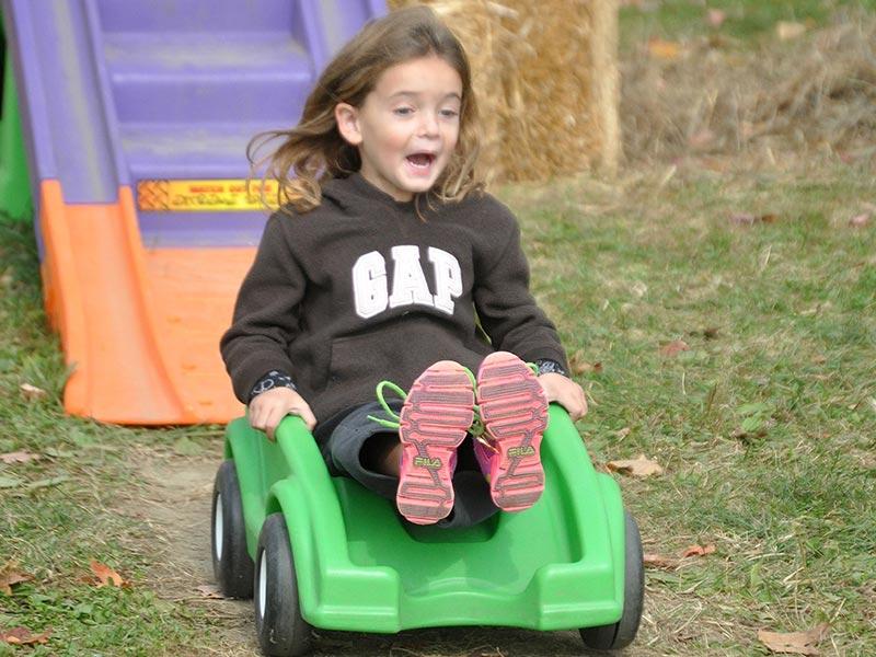 Girl riding rollercoaster at Ellms Farm